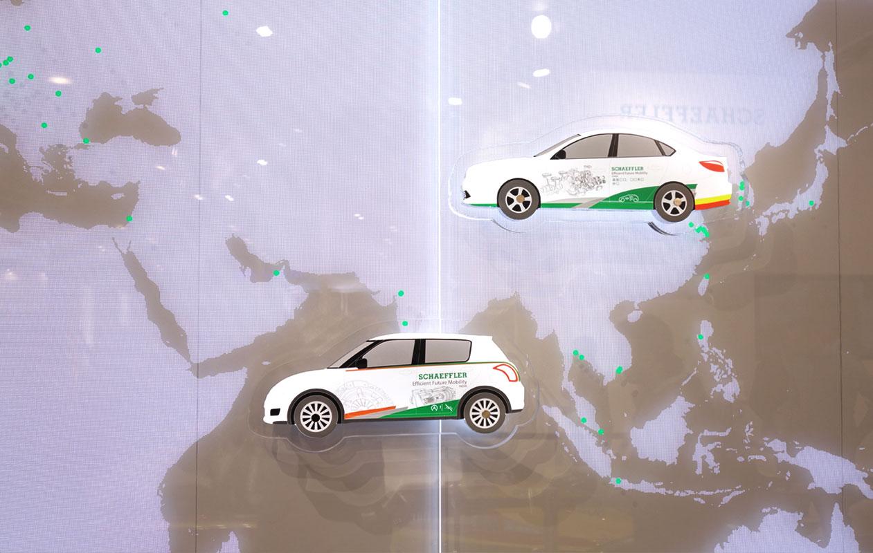 Lightgraphic-Leuchtwand aus lasergraviertem mit LEDs beleuchteten Acrylglasscheiben und aufmontierten aufmontierten Autos aus Lightpanel slim der Marke Designpanel.