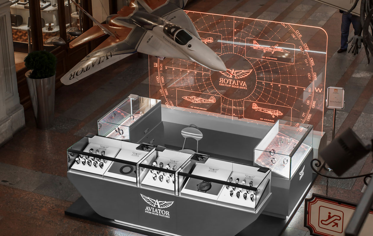 Verkaufsstand mit Lightgraphic-Gravurlicht aus transparentem Plexiglas und beleuchteten Vitrinen am Verkaufsstand der Uhrenmarke Aviator. Hergestellt von axis lichttechnik in Nürnberg.