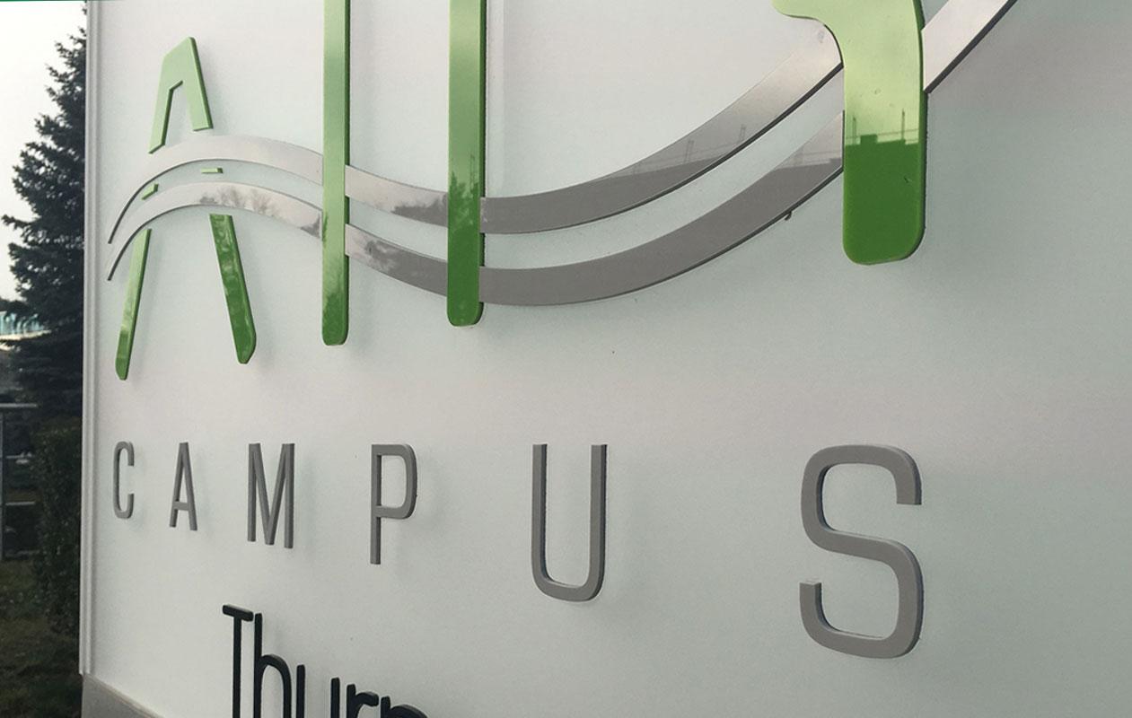 Leitsystem aus LED-Leuchttafeln im Außenbereich des Air Campus in Nürnberg bei Tageslicht mit auswechselbaren, an der Oberfläche fixierten Logos und Buchstaben aus Acrylglas, hergestellt von axis in nürnberg.