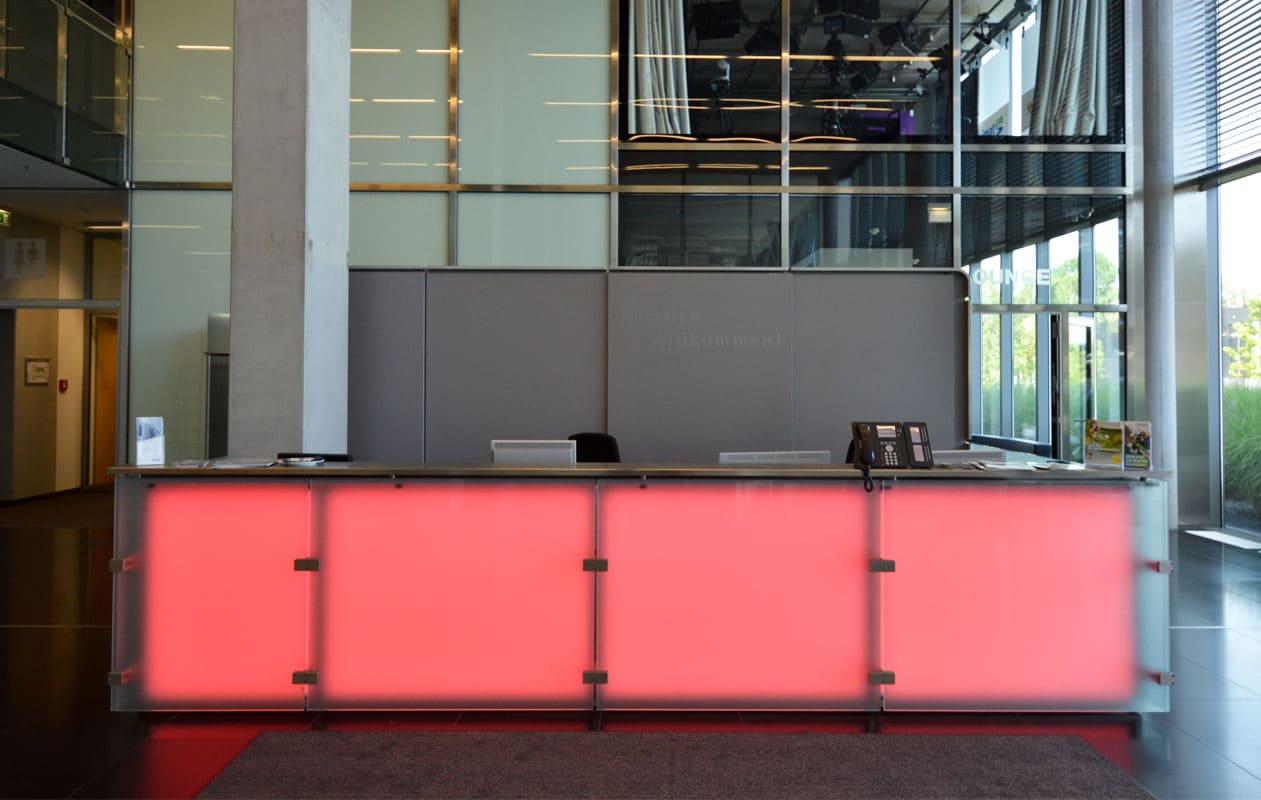 Empfangstresen mit Lichtflächen aus Lightpanels mit LED-Lichttechnik in RGB, die homogen und blendfei leuchten.